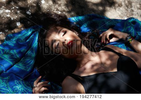 Sensual woman lying down on cliff in studio photo. Beauty concept. Gorgeous brunette with eyes closed lying on blue scarf.