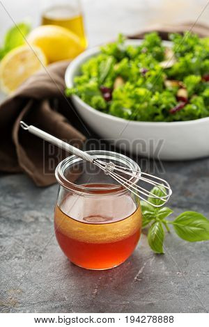 Homemade healthy salad dressing in a small jar with a wisk