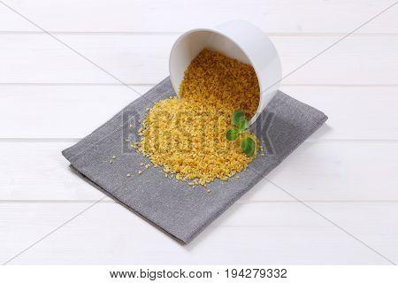 bowl of dry wheat bulgur spilt out on grey place mat