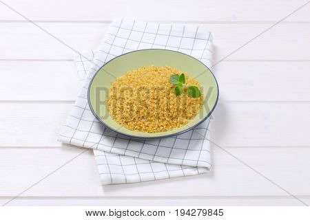 plate of dry wheat bulgur on checkered dishtowel