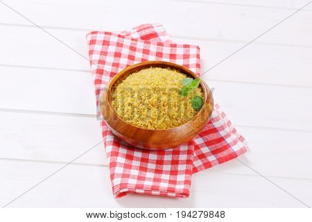 bowl of dry wheat bulgur on checkered dishtowel