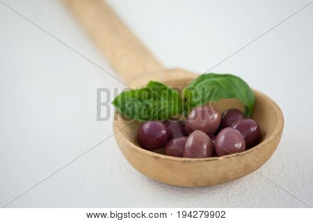 Close up of brown olives with herb in woden laddle on ladle