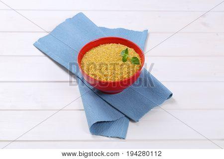 bowl of dry wheat bulgur on blue place mat