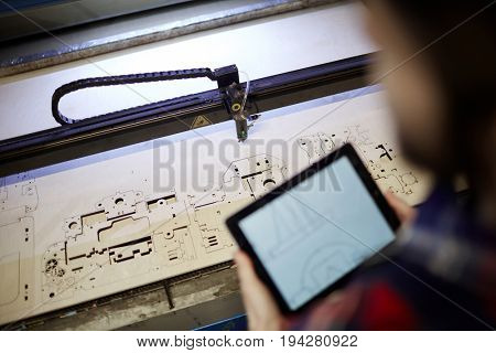 Plywood sheet with cut details and engineer with touchpad near by