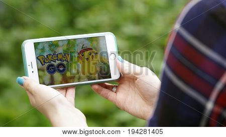 Samara, Russia - July 7, 2017: woman playing pokemon go on his iphone 6s plus. pokemon go multiplayer game with elements of augmented reality. Pikachu in cap of Ashs