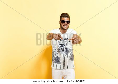 Stylish bearded dude in sunglasses pointing at camera smiling standing against yellow background.