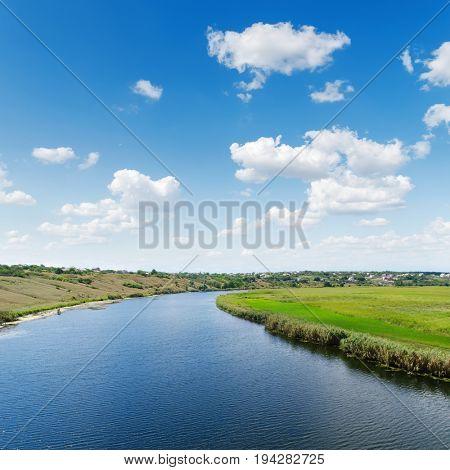 big river in green landscape under white clouds in blue sky