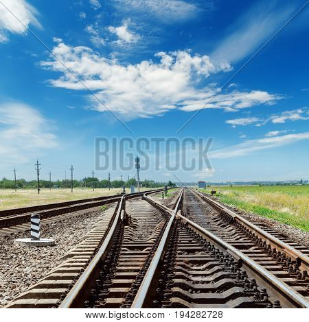 crossing of railroads and blue sky with clouds