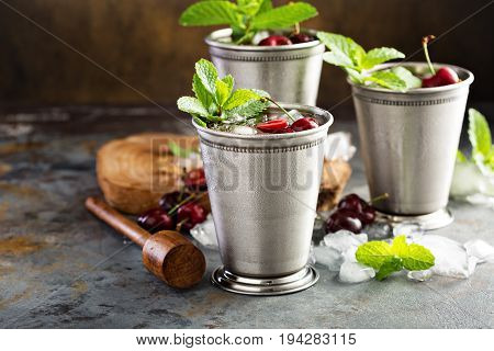Summer mint julep cocktail with sweet cherry