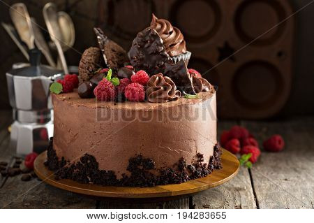 Gourmet chocolate cake topped with frosting, candy and cupcakes