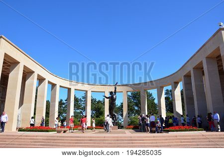 COLLEVILLE-SUR-MER FRANCE - AUG 12: Visitors walk at the memorial in the Normandy American Cemetery and Memorial in Colleville-Sur-Mer France on August 12 2016.