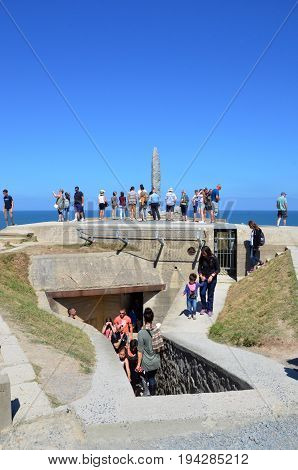 POINTE DU HOC FRANCE - AUG 12: Visitors look at the Ranger Monument at Pointe Du Hoc France on August 12 2016. The Monument sits atop a German observation bunker.
