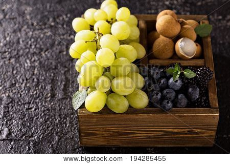 Fresh fruits in wooden box, grapes, longan and blueberry