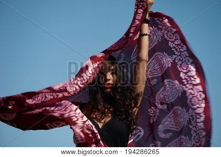 Portrait of attractive young woman with oriental scarf against blue sky with fluttering hair. Female model having fun outdoors.
