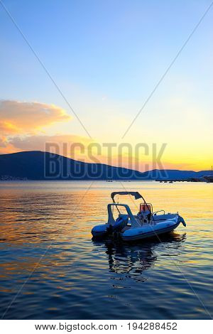 Colorful seascape with boat at sundown