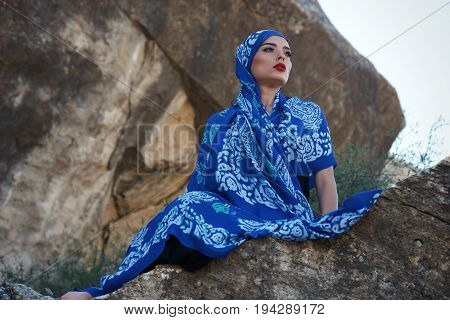 Gorgeous young long hair brunette beauty with slanted head wearing oriental colorful scarf Sits on rocks on a mountain background