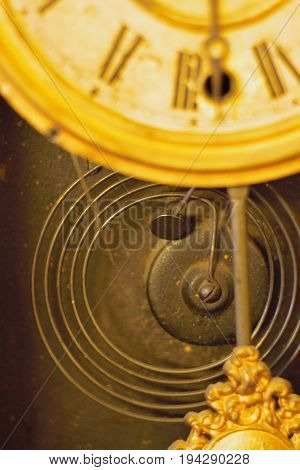 Spring inside old clock with pendulum swinging