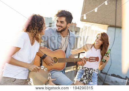 Three young friends having fun at rooftop party playing guitar and singing. Focus on the man playing the guitar