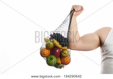 Athlete man flexing his bicep and holding a mesh shopping bag full of fruit isolated on white background with copy space. Helathy eating and detox concept.