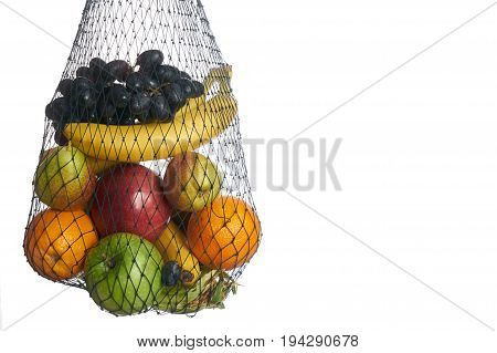 Assorted fruit in mesh grocery bag isolated over white background with copy space. Detox and healthy eating concept. Vegetarian food.