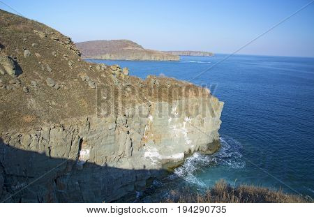 sheer rock, going into the sea, where the birds nest. a bright sunny day