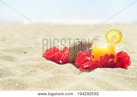 Red Hawaiian lei garland with juice in a jar and coconut on sand on the beach, with ocean on background. Perfect vacation.