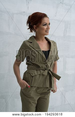 Beautiful brown haired woman in nice khaki jacket and pants smiling studio portrait