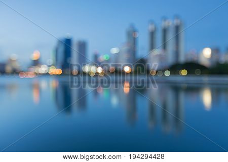 Office building blurred bokeh light with water reflection night view abstract background