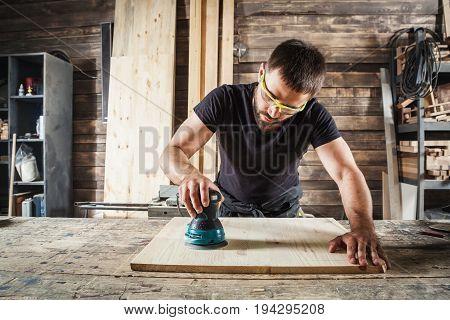 Young man builder carpenter equals polishes wooden board with a random orbit sander in the workshop