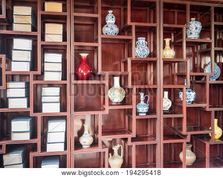 Suzhou, China - Nov 5, 2016: Master of Nets Garden (Wang Shi Yuan), featuring classical Chinese study room with wooden shelves holding vases and books.