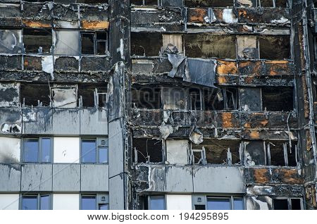 Close up view of the exterior of the Grenfell Tower block of flats in which at least 80 people lost their lives in a fire. Remains of exterior cladding can be seen out the outside of the building this is thought to have increased the spread of the fire.