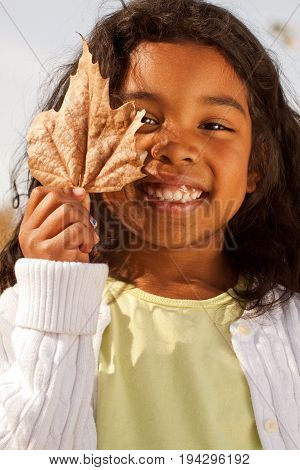Happy little girl outside looking at a leaf.