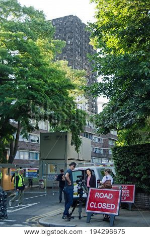 LONDON UK - JULY 5 2017: A Television crew reporting from the site of the Grenfell Tower disaster with construction workers looking on. At least 80 people are feared to have been killed in a fire at the tower block.