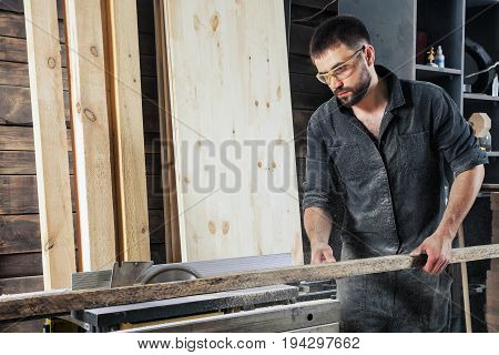 Young male construction worker carpenter sawing a circular saw blade in a beautiful workshop