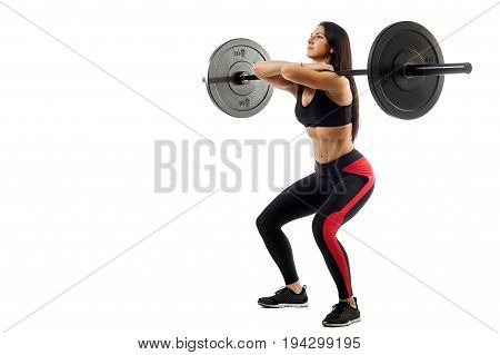 Young athletic brunette woman doing squat with a barbell loki in front of him position of a half-squat on a white isolated background
