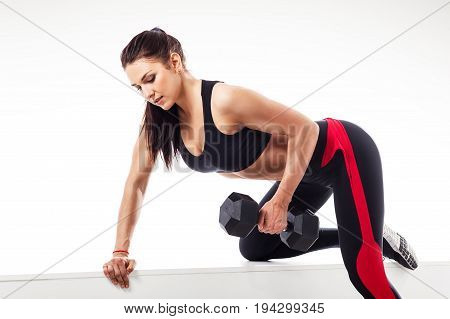 Young athletic brunette woman doing an exercise with a dumbbell on the biceps leaning on a sports bench on a white isolated background