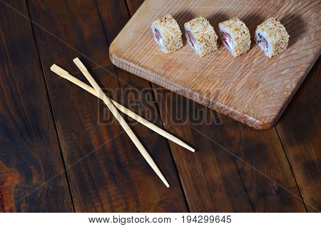 A Detailed Shot Of A Set Of Japanese Sushi Rolls And A Device For Their Use (chopsticks), Which Are