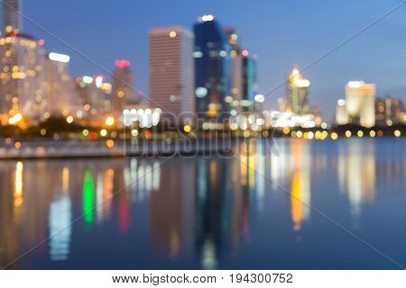 City central business downtown blurred bokeh light with water reflection at twilight abstract background