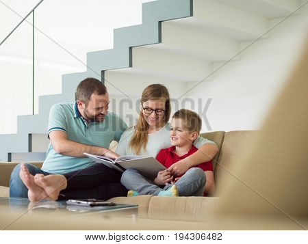 happy young family with little boy enjoys in the modern living room of their luxury home villa