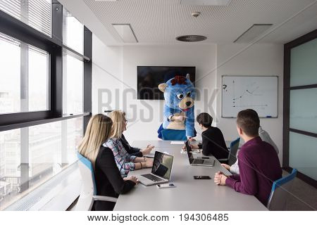 Boss dressed as teddy bear having fun with bussines people in modern corporate office
