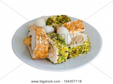 Traditional Turkish Delight Lokum on White Plate Isolated. Sweet Rolls of Rahat Lokum with Nut Paste Hazelnut Pistachio and Sesame. Ramadan Sweets poster