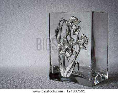 rectangular clear glass vase with floral decoration in relief at an angle against a white background, with space for overprinting text