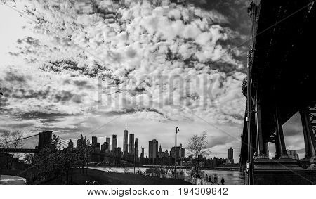 Manhattan bridge and Brooklyn bridge at park and buildings in Manhattan with cloudy sky in black and white style