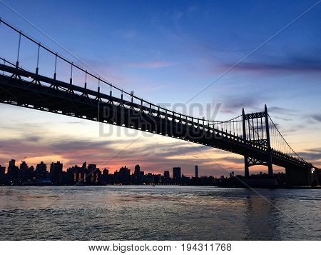 Silhouette of Triborough bridge and the city before sunset, Astoria park, New York
