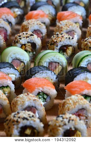 Sushi Set Of A Number Of Rolls Is Located On A Wooden Cutting Board On A Table In The Kitchen Of A S