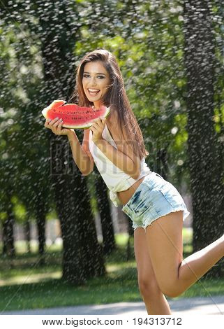 Portrait of young sexy woman in spray of water with watermelon.She has a good gentle skin, her hair flying, and she smiles.Happy young woman  in park. Youth lifestyle. Happiness, joy, summer concept.