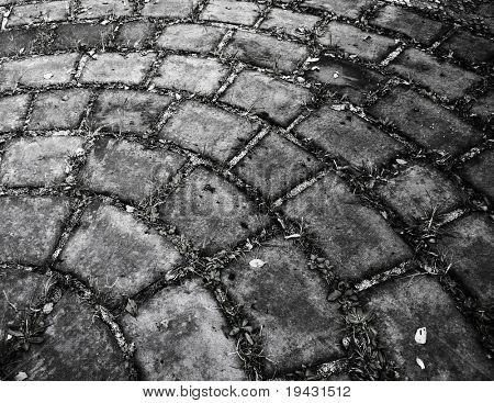 Circular cobble stone in grungy monotone.