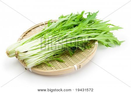 Mizuna (kyona, Xiu Cai, Kyona, Japanese Mustard) on a bamboo tray, isolated on white with natural shadows.