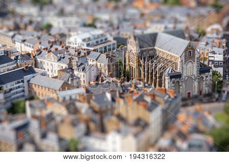 Aerial cityscape view with beautiful buildings and saint Nicolas cathedral in Nantes city during the sunny weather in France. Tilt shift image technic
