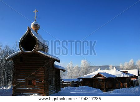 Taltsy. Irkutsk. Russia - January 7, 2014:Traditional Russian wooden architecture in Siberia. Church, house of logs and fence. View winter. Taltsy. Irkutsk. Russia.
